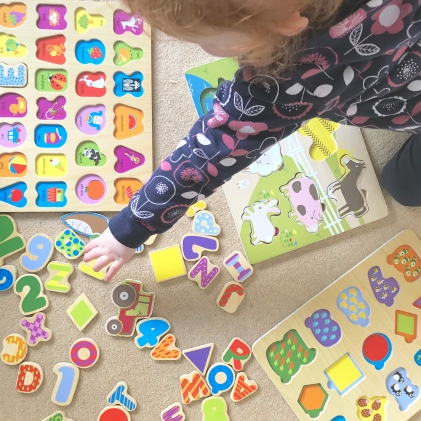 A child doing her wooden puzzles, the puzzle pieces are scattered on the floor