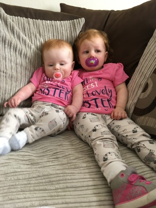 A photo of two children born 13 months apart wearing matching outfits, a pink t-shirt and leggings with cats and dogs on