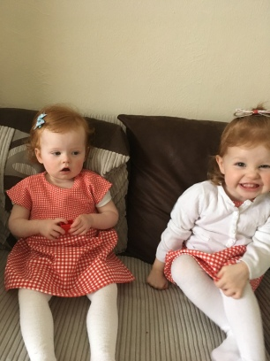 A photo of two girls born 13months apart wearing matching red dresses