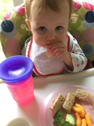 Toddler eating sandwich, cucumber, ham and cheese puffs in a high chair with her pink non spill up