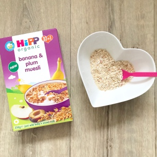 Hipp organic banana and plum musli in a heart shaped bowl with a pink spoon