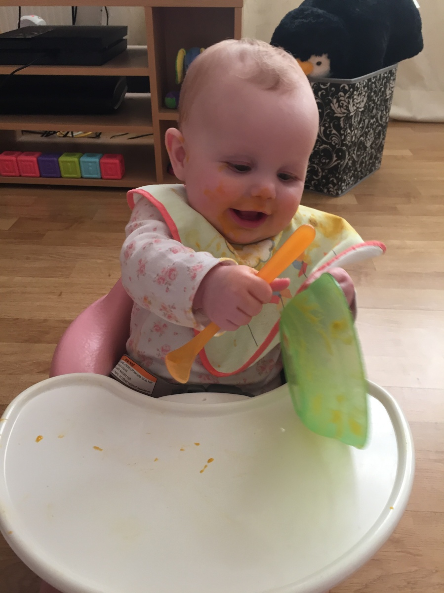 Baby has finished their meal and is playing the the food bowl and spoon while sat in the baby seat
